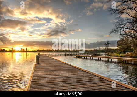 Sunset over lake Kralingse plas and the Rotterdam skyline as seen from one of the wooden walkways - Stock Photo