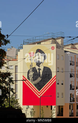 Sreet art as memorial of the Portuguese Carnation Revolution. Women soldier with a gun with a carnation flower in it  on an apartment building in Lisb - Stock Photo