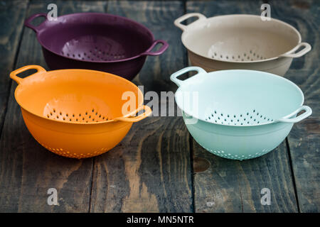 Colorful plastic colanders with handles on blue wooden background - Stock Photo