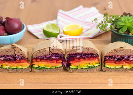 Rainbow salad sandwiches with homemade buckwheat bread, displayed on a wooden board. This fresh healthy lunch is low calorie, dairy free & gluten free. - Stock Photo