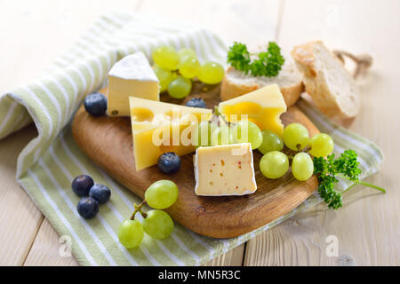 Cheese snack with serveral kinds, served with bread and grapes on a wooden cutting board - Stock Photo