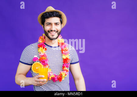 Handsome bearded man dressed in lei on neck and hat and holds orange drink on purple background, vacation time concept, isolated studio shot - Stock Photo