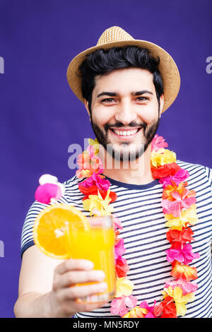 Bearded man dressed in lei on neck and hat and holds orange drink on purple background, vacation time concept, isolated studio shot - Stock Photo