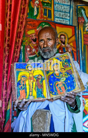 Priest of the rock-hewn church Mikael Mellehayzengi showing the book Miracles of Maria with colorful hand-painted designs on parchment,Ethiopia - Stock Photo