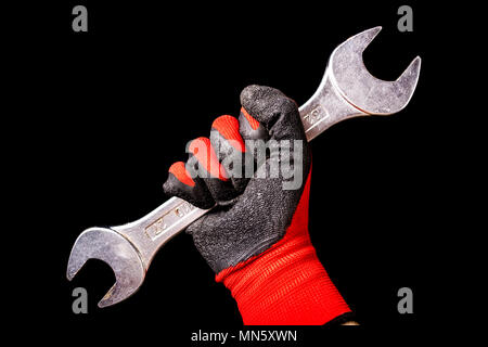 Hand with protective gloves holding wrench tool isolated on black background. Close up - Stock Photo