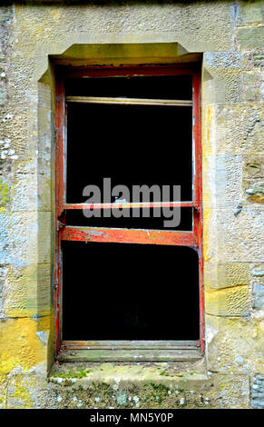 Red rotting wooden window frames of derelict building - Stock Photo
