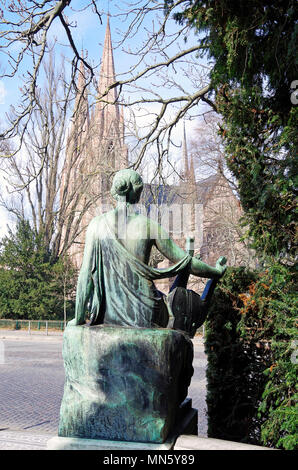 Polyhymnia, the Muse of lyrical Poetry, part of the Goethe Memorial in Strasbourg contemplating the Protestant church of St Paul - Stock Photo