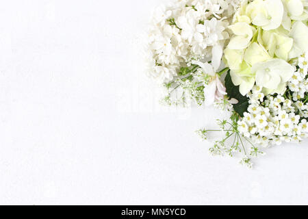 Styled stock photo. Decorative floral composition. Wild wedding or birthday bouquet of blossoming white lilac, apple tree branch, hydrangea, spirea flowers. White table background. Flat lay - Stock Photo