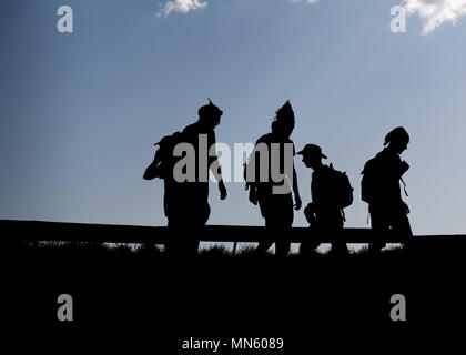 Hikers silhouettes thru thetop of the mountain over blue sky background - Stock Photo