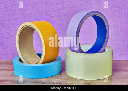 Four rolls of adhesive tape of different colors and for different purposes lie on a table on a lilac background. - Stock Photo