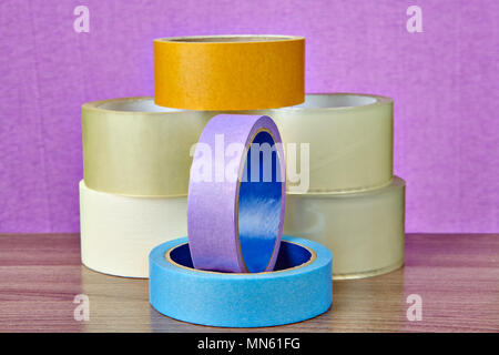 Several rolls of duct tape in different colors and for different purposes are on the table on a purple background. - Stock Photo