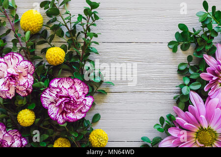 Mixed Flowers on White Table including Chrysanthemums, Carnations and Craspedia - Stock Photo