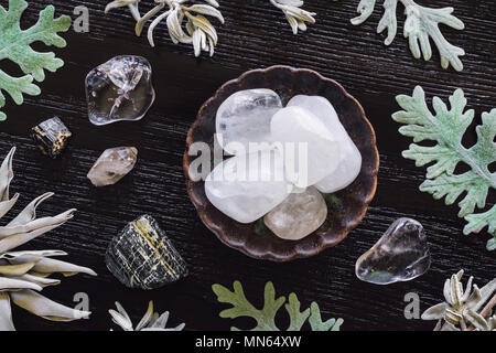 Quartz and Black Tourmaline on Dark Table with Dusty Miller and Sage - Stock Photo