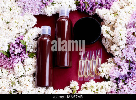 Vials with cosmetics in fresh flowers on a red background. - Stock Photo