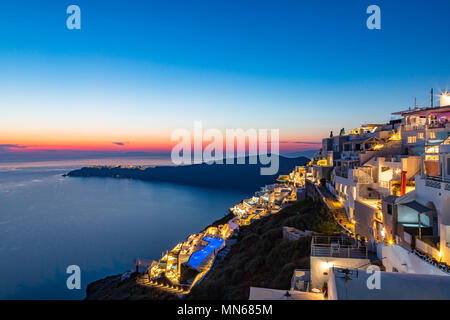 Santorini Sunset. Beautiful colours spread across the sky over the Greek island of Santorini. The flickering lights wash the faces of the white washed - Stock Photo