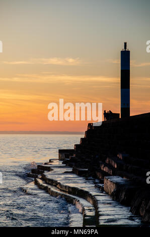 Aberystwyth Sunset at the lighthouse. A group of people stand at the end looking over the water and gazing at the sunset. - Stock Photo