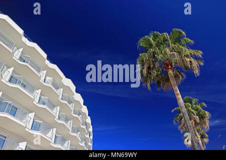 Hotel facade against deep blue sky, with palm trees - Stock Photo