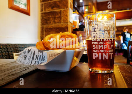 A pint of beer and onion rings on a table. The pub is the Peacock Inn in Bakewell and the beer is locally brewed. - Stock Photo