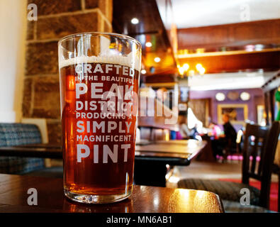 A pint of beer on a table. The pub is the Peacock Inn in Bakewell and the beer is locally brewed. - Stock Photo