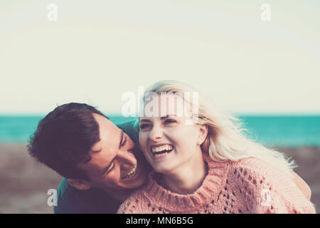 young caucasian couple blonde and black hair stay together with joy and love outdoor with beach and ocean in background. leisure vacation concept with - Stock Photo