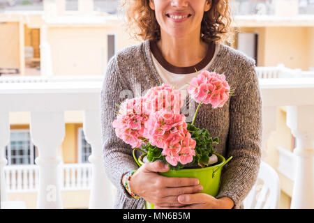 beautiful middle age caucasian woman smile and protect her flowers having care of them with an hug. outdoor terrace at home scene with colors of sprin - Stock Photo