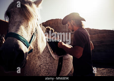 beautiful cowboy scene with mountains on the background and backlight from the sunset for beautiful young man blonde long hair and best friend horse t - Stock Photo