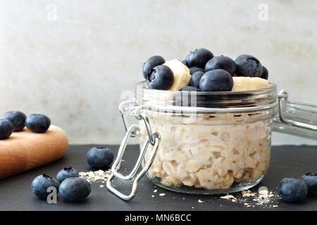Jar of overnight oats with fresh blueberries and bananas, scene with white and black stone background - Stock Photo
