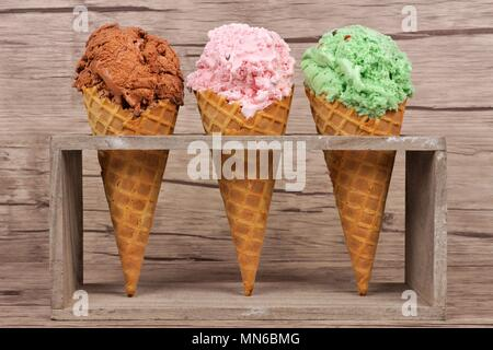 Chocolate, cherry and pistachio ice cream in waffle cones in rustic holder over a wood background - Stock Photo