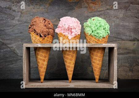 Chocolate, cherry and pistachio ice cream in waffle cones in rustic wood holder over a slate background - Stock Photo