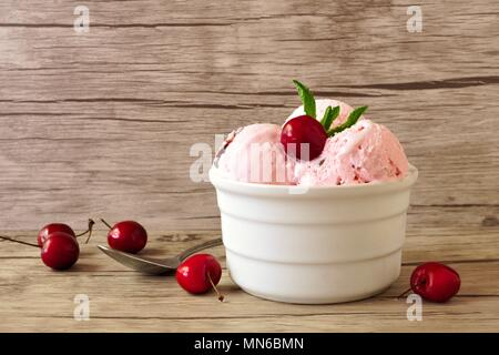 Bowl of cherry chocolate ice cream, still life on a wooden background - Stock Photo