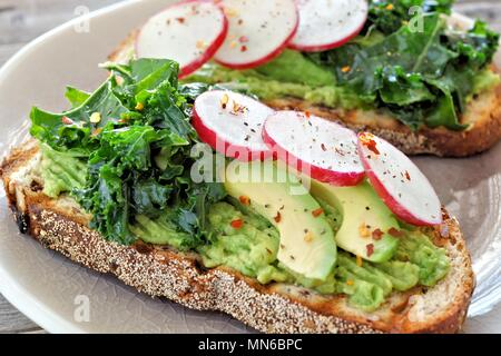 Healthy avocado toast close up with kale and radish on whole grain bread - Stock Photo