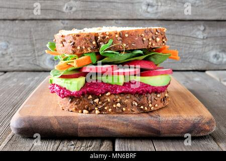 Superfood sandwich with beet hummus, avocado, vegetables and greens, on whole grain bread against a wooden background - Stock Photo