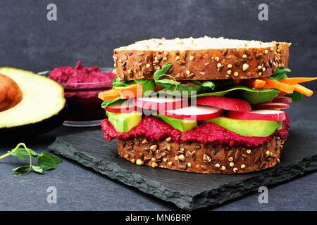 Superfood sandwich with beet hummus, avocado, vegetables and greens, on whole grain bread against a slate background - Stock Photo