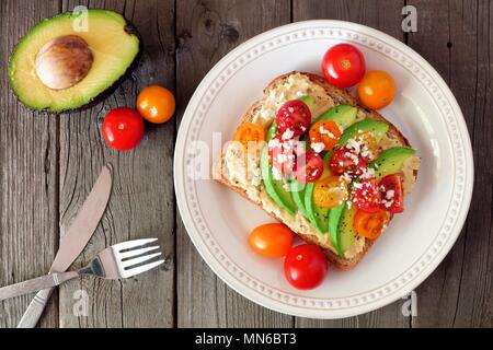 Avocado toast with hummus and tomatoes on plate, above scene on old wood background - Stock Photo