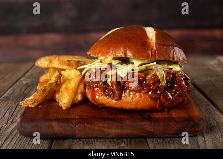 Pulled pork sandwich on pretzel bun with potato wedges on a serving board with wood background - Stock Photo