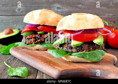 Veggie bean and sweet potato burgers with avocado and spinach against a rustic wooden background - Stock Photo