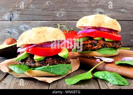 Two vegetarian bean and sweet potato burgers with avocado and spinach against a rustic wooden background - Stock Photo