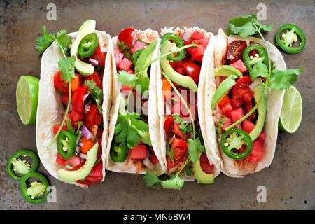 Spicy fish tacos with watermelon salsa and avocados, above view on rustic metallic background - Stock Photo