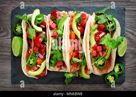 Spicy fish tacos with watermelon salsa and avocados, overhead view on slate server - Stock Photo