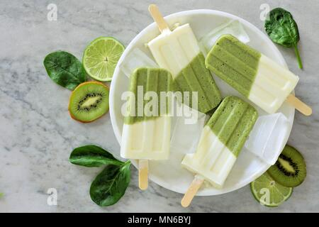 Healthy green smoothie popsicles with kiwi, lime and spinach on a white marble plate, overhead view - Stock Photo