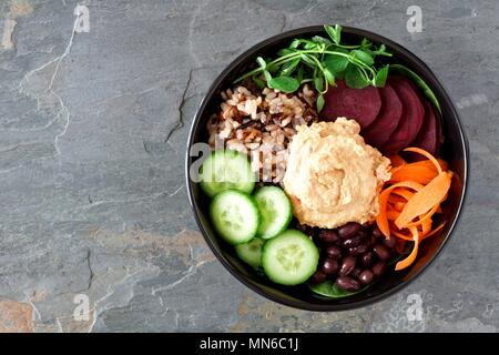 Healthy vegetarian salad bowl with hummus, beans, wild rice, beets, carrots, cucumbers and pea shoots. Above view on slate background. - Stock Photo