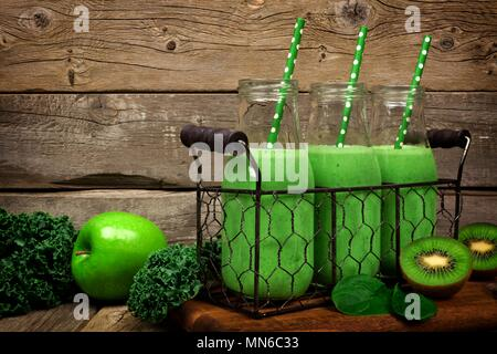 Green smoothies in milk bottles in a vintage wire basket against a rustic wood background - Stock Photo