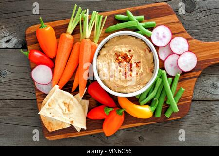 Hummus dip with a serving platter of fresh vegetables, above view on a wood background - Stock Photo