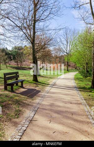 Garden or park bench near an empty dirt path, track, trail or pathway through the trees and green grass lawn in Parque da Devesa Urban Park. Vila Nova - Stock Photo