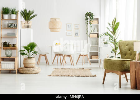 ... Lamp On Wooden Stool And Green Armchair In Multifunctional Dining Room  Interior With Pouf, Plants
