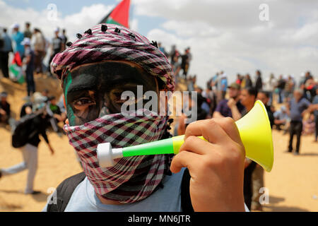 GAZA, PALESTINIAN TERRITORIES - 14 MAY 2018 Palestinian demonstrators gesture towards Israeli forces during clashes along the border with the Gaza Str - Stock Photo