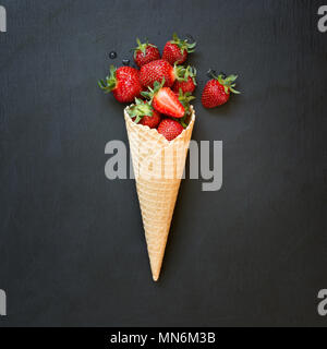 Fresh organic strawberry in ice cream cone on black. - Stock Photo