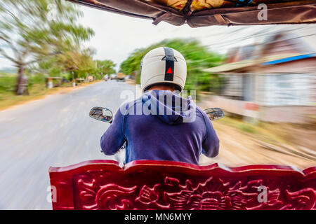 Riding in a tuk-tuk, a motorcycle with a trailer attached for transporting passengers, the de-facto taxi in Cambodia and most of South East Asia, Siem Reap, Cambodia - Stock Photo