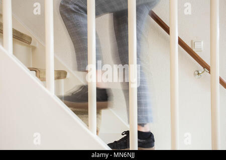 Young adult person walking up the stairs in house - Stock Photo