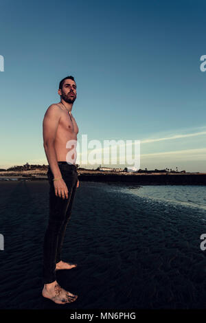Young man standing without shirt in the sand of the beach in Sanlucar de Barrameda - Stock Photo